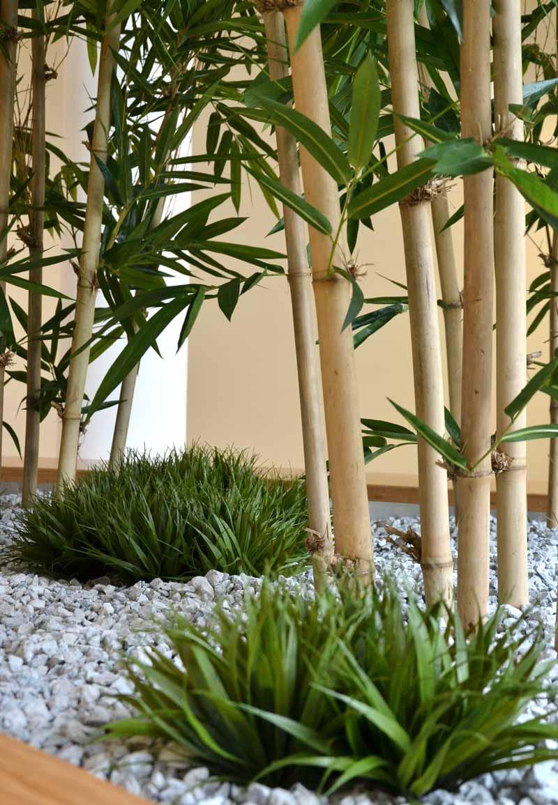 Gräser und Bambus (Kunstpflanzen) als langfristige Bepflanzung von einem Pflanzbeet in einem Bürogebäude
